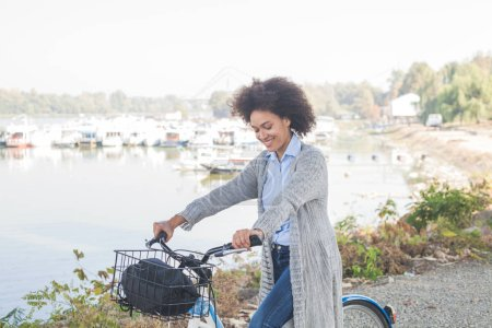 Photo for Relaxed Afro woman with bicycle enjoying free time near river. - Royalty Free Image