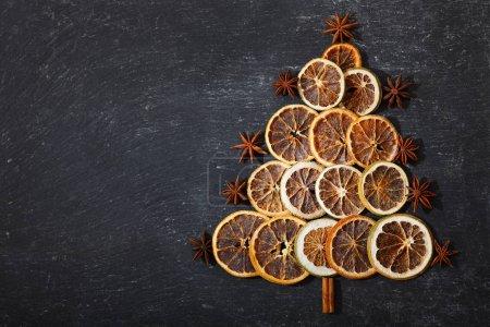 Photo pour Arbre de Noël en fruits secs, bâtonnets de cannelle et étoile d'anis sur la table noire, vue du dessus avec espace de copie - image libre de droit