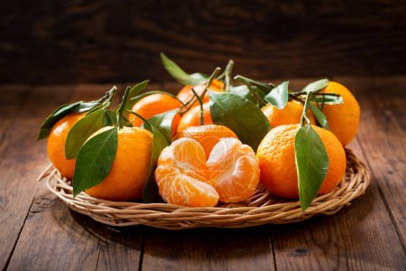 Fresh mandarin oranges fruit or tangerines with leaves on wooden table