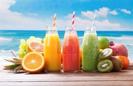 Photo pour Bouteilles de jus de fruits et smoothie aux fruits frais sur table en bois - image libre de droit