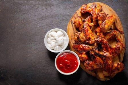 Photo pour Ailes de poulet grillées sur une planche en bois, vue sur le dessus - image libre de droit