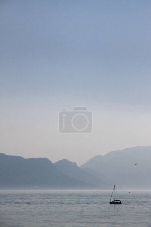 Photo for Sailing boat sailing without wind on inboard engine with mist behind it - Royalty Free Image