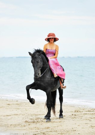 riding girl and her black stallion on the beach