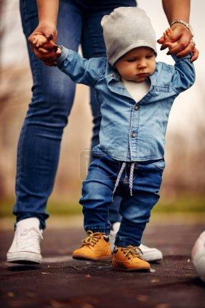 Photo pour Mère aide son petit garçon à faire ses premiers pas - image libre de droit