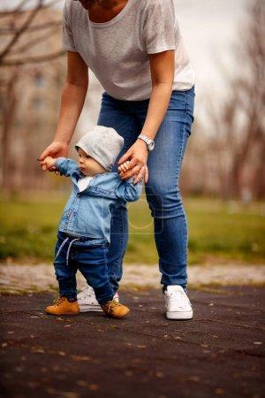 Photo pour Maman enseignant les premiers pas de son fils mignon dans le parc - image libre de droit