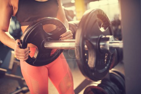 Photo for Preparing barbell for exercise in gym - Royalty Free Image