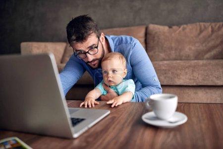 Photo pour Jeune homme d'affaires utilisant un ordinateur portable pour travailler à la maison tout en s'occupant de son fils bébé - image libre de droit