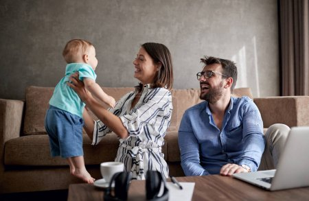 Photo pour Heureux jeune homme et femme avec bébé travaillant à la maison à l'aide d'un ordinateur portable - image libre de droit