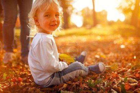 Photo pour Enfant garçon souriant dans le parc d'automne. Le concept d'enfance, de famille et d'enfant - image libre de droit