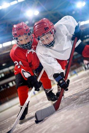 Foto de Jugador de hockey de jóvenes manejo de puck en el hielo - Imagen libre de derechos