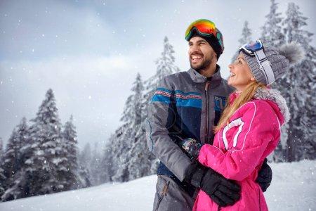 Photo pour Amour couple bénéficiant d'ensemble sur les vacances d'hiver sur la montagne de neige - image libre de droit
