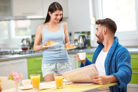 Photo for Happy woman serving rich breakfast to husband - Royalty Free Image