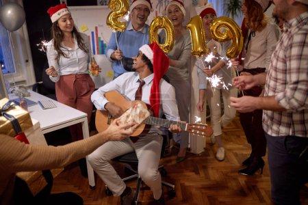 Photo pour Gens de groupe d'affaires prospères en bonnet de Noël à la fête de Noël au bureau célèbre avec la chanson - image libre de droit