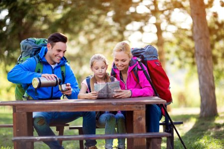 Photo for Hiking family relax sitting and look on the map in the forest - Royalty Free Image