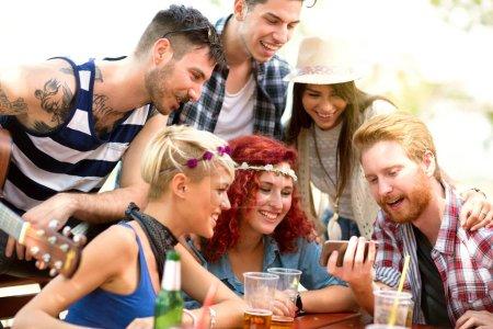 Photo pour Les jeunes s'amusent tout en regardant quelque chose d'intéressant sur le téléphone mobile ses amis en plein air - image libre de droit