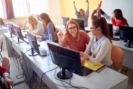 Photo for Smiling students sitting together at table using computer in class on university campus - Royalty Free Image