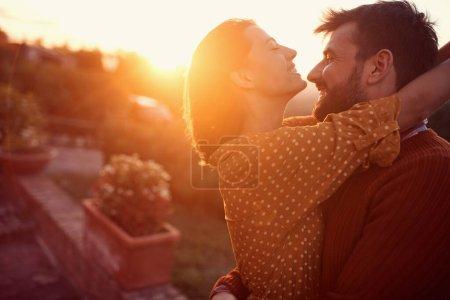 Photo pour Souriant jeune couple étreignant et embrassant au coucher du soleil - image libre de droit