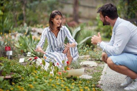 Photo pour Sortie architecte paysagiste expliquant de nouvelles ides à un collègue masculin sur l'aménagement d'un parc botanique - image libre de droit