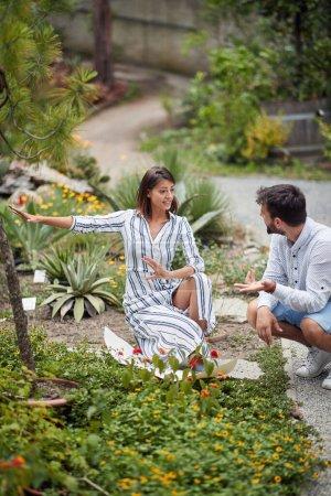 Photo pour Belle jeune architecte paysagiste sexy expliquant de nouvelles ides à un collègue masculin sur l'organisation du jardin botanique - image libre de droit
