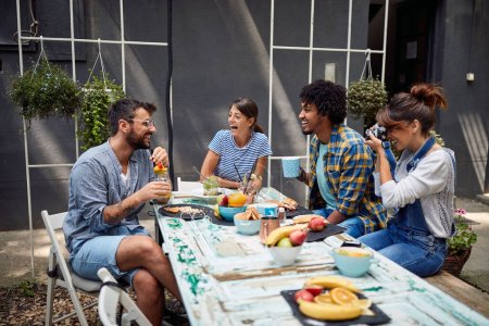 Photo for Girl is taking a photo of friends of her in relaxed atmosphere - Royalty Free Image