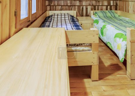 Bedroom with two beds in a wooden chalet.