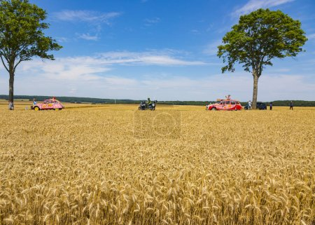 Vendeuvre-sur-Barse, France - 6 July, 2017: Two vehicles of Cochonou passes through a region of wheat fields in the Publicity Caravan before the cyclists during the stage 6 of Tour de France 2017. Cochonou is an important French brand of short dry sa