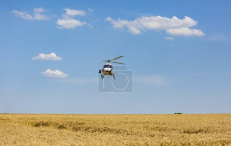 Vendeuvre-sur-Barse, France - 6 July, 2017: Image of a helicopter of France Television broadcasting live images above a region of wheat fields during the stage 6 of Tour de France 2017.