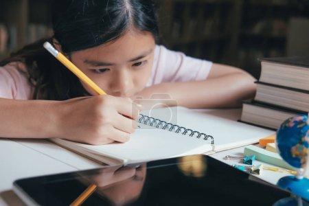 Photo pour Concept d'éducation. Fille lire et écrire et faire des devoirs à la bibliothèque de l'école. Etude et apprentissage de seft - image libre de droit