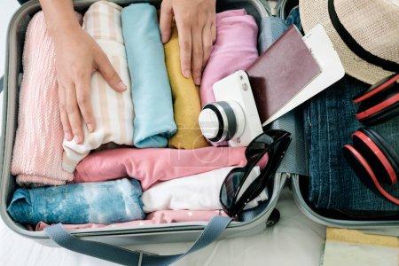 Photo pour Préparation pour les vacances ou les voyages. Emballage de ses vêtements et des choses dans une grande valise ouverte qui presque déjà plein . - image libre de droit