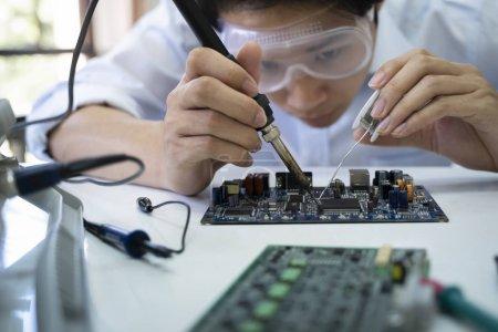 Photo pour Le technicien vérifie l'appareil électronique. Carte de circuit imprimé pour le robot . - image libre de droit