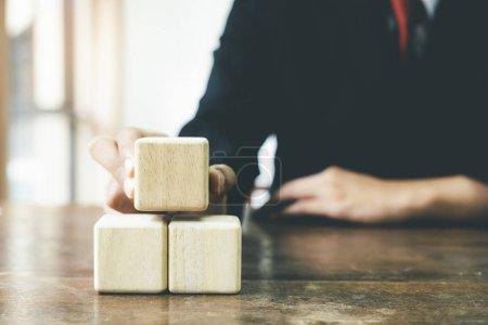 Businessman hand arranging wood block business strategy.