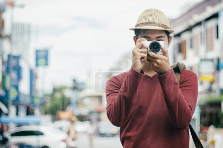 Photo for Traveling male tourist backpackers taking photo.  City travel and travel concept. - Royalty Free Image