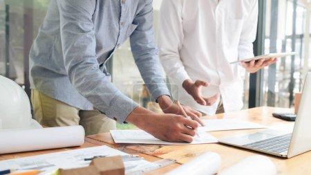 Photo pour Image d'une réunion d'ingénieurs pour un projet architectural travaillant avec des partenaires et des outils d'ingénierie sur le lieu de travail . - image libre de droit