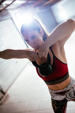 Young muscular woman doing high pull exercise with kettlebell on hard training