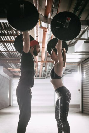 Young muscular couple doing overhead squat exercise with barbell on cross training