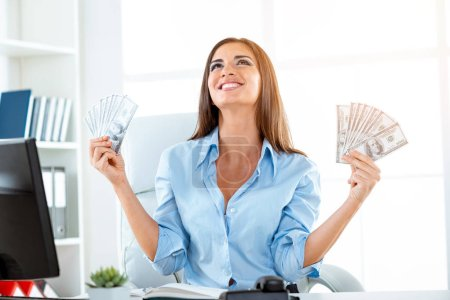 Young businesswoman holding money in hands