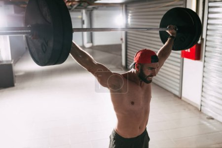 Photo for Young muscular man doing high pull exercise with barbell on cross training - Royalty Free Image