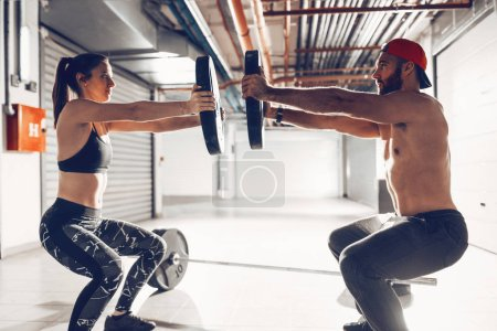Photo for Young muscular couple doing hard exercise with weights on cross training - Royalty Free Image