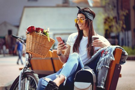 young woman with bike with flower basket using smartphone and drinking coffee