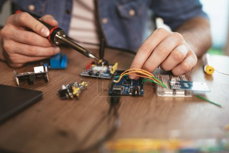 Photo for Close view of male hands soldering circuit board by soldering iron on table - Royalty Free Image