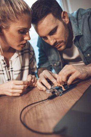 Photo pour Deux technicien de partenaires de jeunes entreprises axées sur la réparation de matériel électronique - image libre de droit