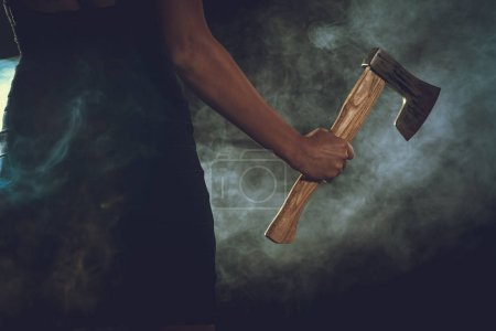 Close view of woman holding ax in smoky dark room...