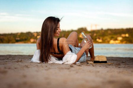Young woman with straw hat drinking beer on beach at sunset
