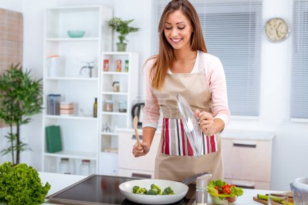 Photo for Young woman cooking healthy broccoli in kitchen - Royalty Free Image