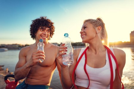 Young fitness couple resting after hard training by river at sunset drinking water