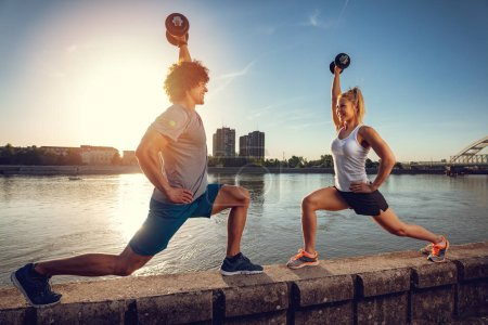 Young fitness couple doing workout with dumbbells by river at sunset