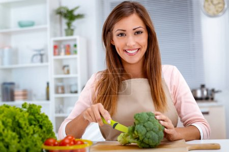 Photo for Young woman preparing vegetarian food on kitchen table - Royalty Free Image