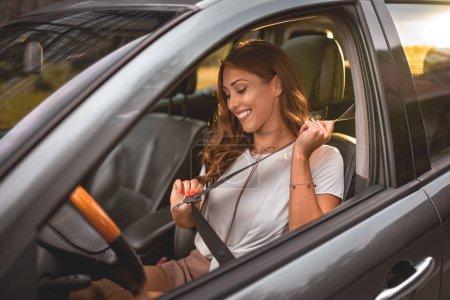 Photo pour Femme d'affaires belle assis sur le siège auto et la ceinture de fixation - image libre de droit