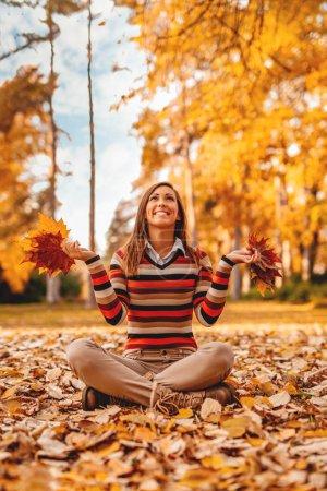 Photo pour Jeune femme assise sur le sol couverte de feuilles et s'amusant - image libre de droit