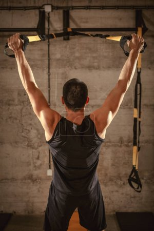 Young muscular man training in gym